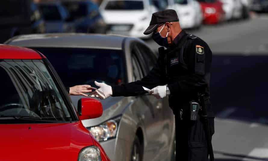 A police officer checks the papers of a driver in Spain