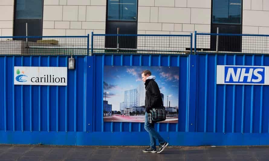 A pedestrian walks past hoarding showing the branding of British construction company Carillion at the collapsed company's construction site