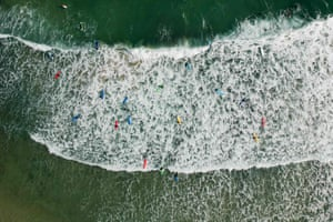 Hong KongSurfers paddle out to sea as waves break on a beach in Hong Kong.