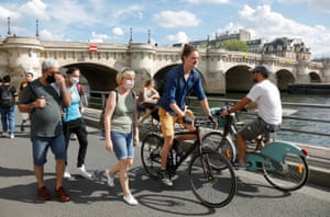Pedestrians wearing protective face masks walk along the Seine river banks, as France reinforces mask-wearing as part of efforts to curb a resurgence of coronavirus across the country, in Paris, France, 15 August, 2020.
