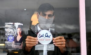 Rishi Sunak in a face mask sticking an 'Eat out to help out' sticker in a window