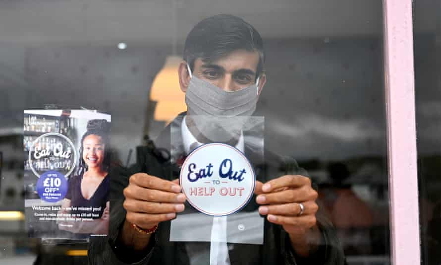 Rishi Sunak puts up a eat out to help out sticker at a restaraunt.
