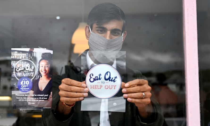 Rishi Sunak places an Eat out to help out sticker in the window of a business in Rothesay on the Isle of Bute, August 2020