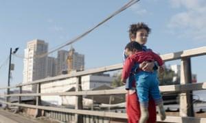 Zain (Zain Al Rafeea) carries infant Yonas to safety in Capernaum.