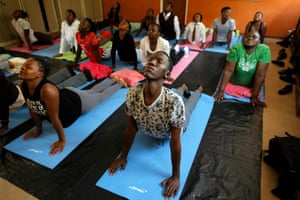 Children at the Minerva secondary school do the upward facing dog during an afternoon class