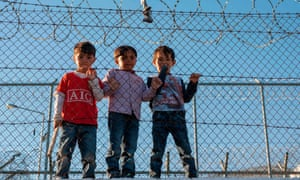 Children stand behind a fence inside the Moria refugee camp on Lesbos.