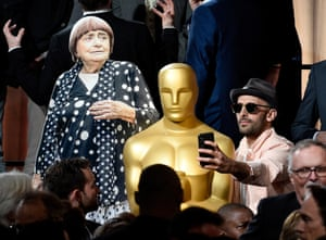 Artist/filmmaker JR (right) takes a selfie with an Oscar statue and a cardboard cutout of collaborator Agnes Varda during the 90th Annual Academy Awards Nominee Luncheon in 2018