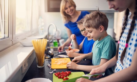 Kids preparing lunchThree kids are cooking today! Mother is overseeing as a teenage girl and her two brother are chopping and mixing ingredients for family lunch. Nikon D850