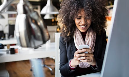 Young businesswomen texting on smartphone in the office.
