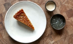 A slice of treacle tart on a round white plate, with a small round pot of lemon jelly and another of Earl Grey cream.