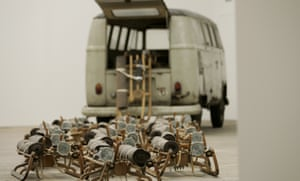 Sledges, resembling a pack of dogs, tumble from the back of a VW van in The Pack, a 1969 work by Joseph Beuys