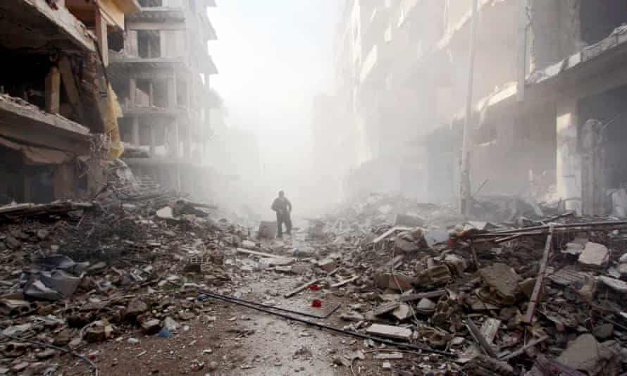 A man walks among the rubble of collapsed buildings in Douma after what activists said were airstrikes by forces loyal to Assad earlier this year.