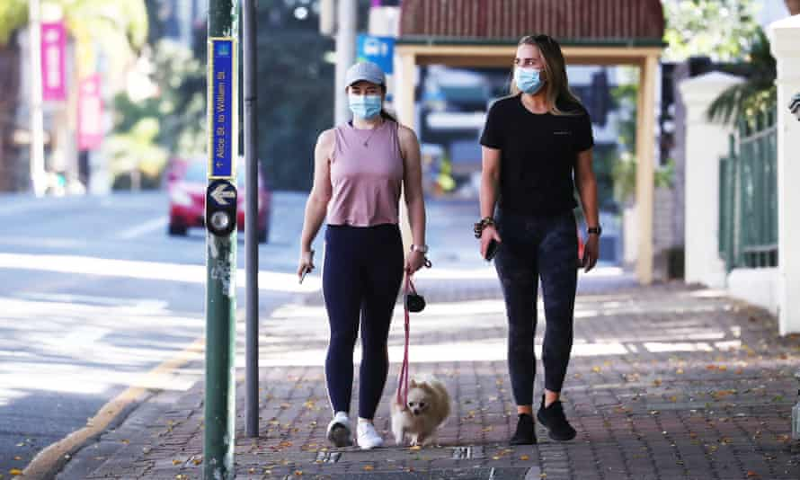 Two people walk in Brisbane on Sunday on the first full day of a Covid lockdown.