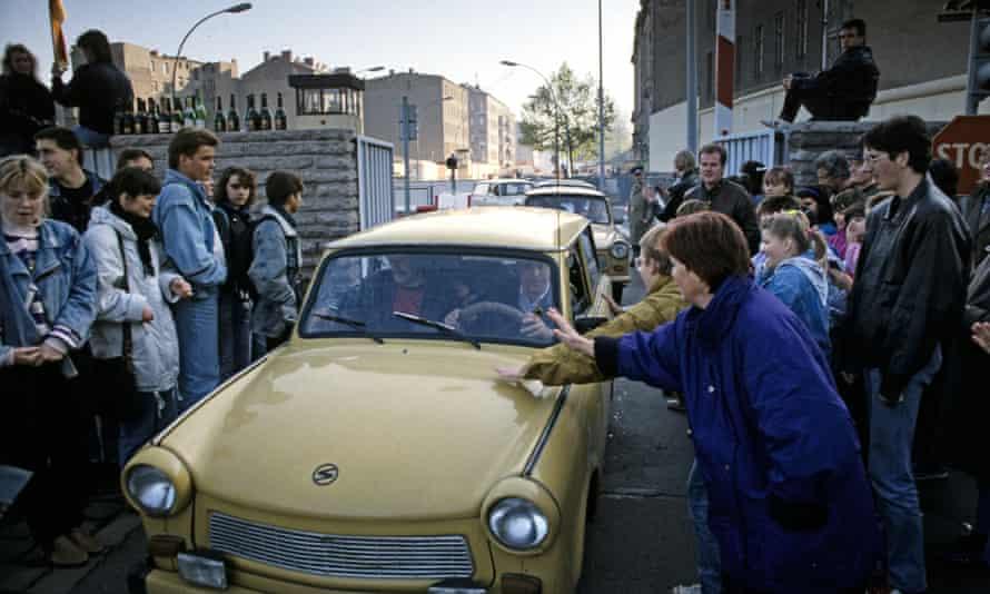 cars drive across berlin wall