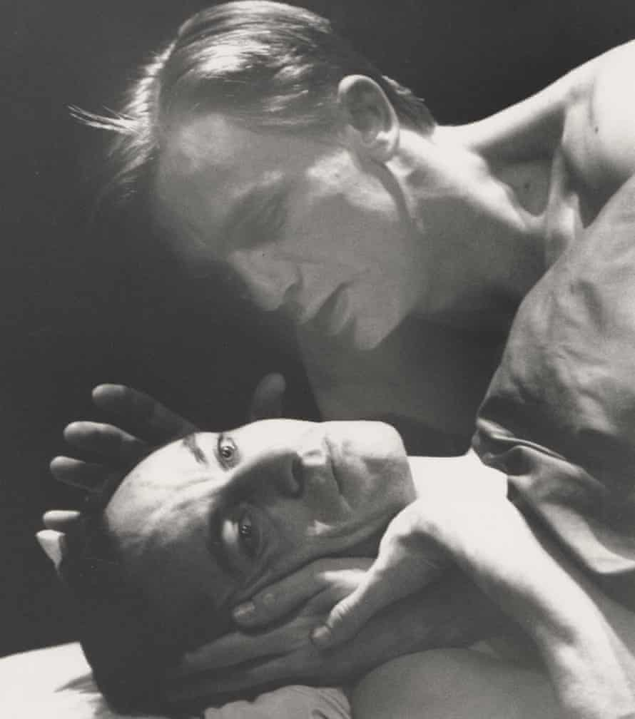 Daniel Craig holding Jason Isaacs' face as they lie together in Angels In America