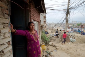 """Rambika Thapa Magar stands outside her one room home on the edge of Kathmandu's ringroad. The expanded road is due to cut through the middle of the house. """"We have been told to evacuate. The demolition could started at any time, maybe while we are sleeping. We have nowhere else to go,"""" said Rambika"""