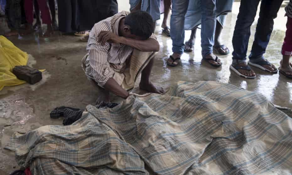 People mourn next to the bodies of relatives after a boat sank in rough seas off the coast of Bangladesh.