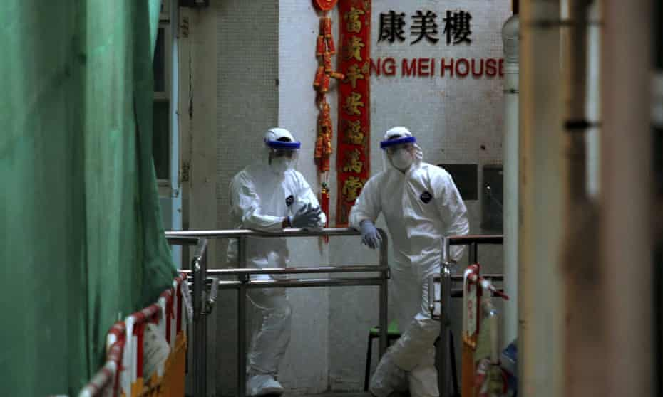 Personnel in protective suits during the evacuation of a public housing estate in Hong Kong.