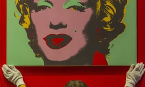 A curator hangs one of 10 screenprints of Marylin Monroe by Andy Warhol.