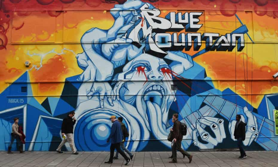 People walk past graffiti on a building in the Stokes Croft area of Bristol. England. Stokes Croft and surrounding areas in Bristol are renowned for their graffiti and street art scene.