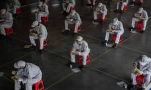 Workers at Dongfeng Honda in Wuhan eat lunch while maintaining a safe distance.