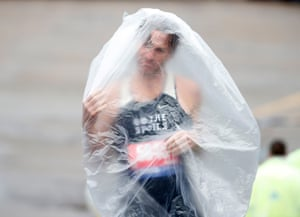 Runner Kyle Rodemacher struggles with his poncho prior to the 2019 Boston Marathon