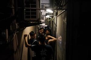 People queue along a narrow passageway outside a ramen restaurant