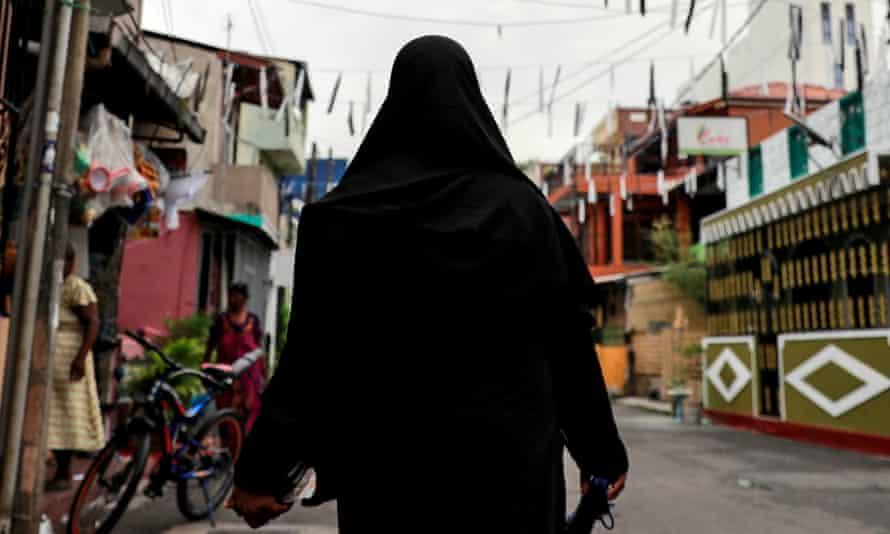 Woman in burqa walking down a street in Colombo, Sri Lanka