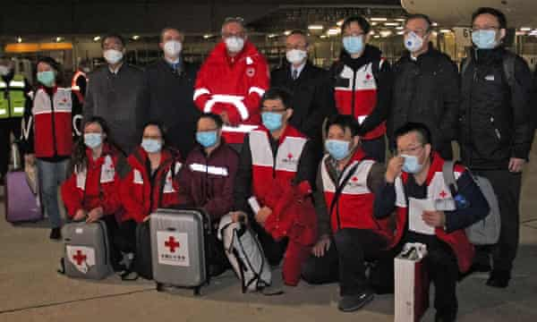 Chinese medics posing on 13 March after arriving in Rome from Shanghai to help fight the coronavirus.