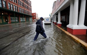 A postman walks through the flooded streets from Tropical Depression Imelda as he delivers mail Wednesday in Galveston, Texas.