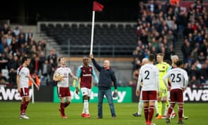A West Ham supporter stands on the pitch holding a corner flag aloft as ugly scenes overshadowed the match.