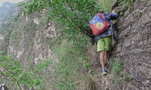 A boy on a cliff on his way home in Zhaojue county.