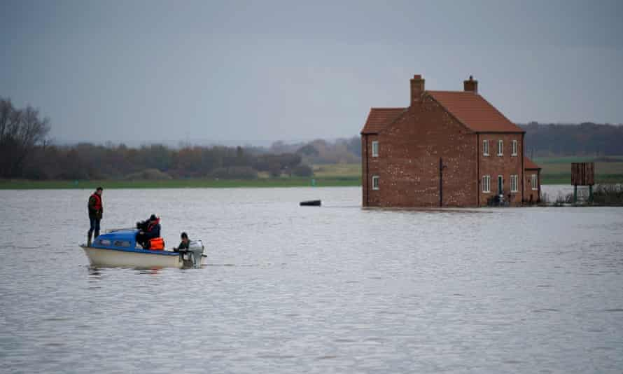 Farmer Henry Ward stands on a boat, the only access to his flood-marooned farm at Bardney, near Lincoln, after the Barlings Eau broke its banks on November 15.