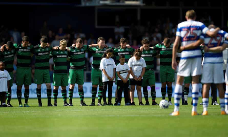 The teams hold a minute's silence for victims of the fire before kick-off
