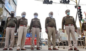 Police stand guard at traffic lights on the first day of a 21-day government-imposed nationwide lockdown in India.