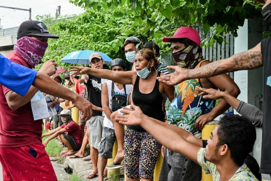 A Kalinga Center representative distributes face masks as hundreds of homeless line up to get food and hygiene packs.