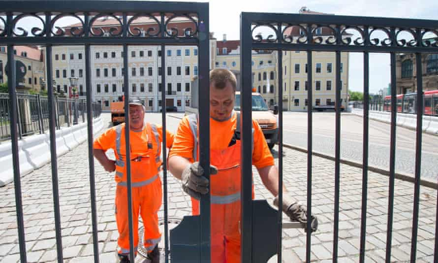 Workers erect a security fence outside of the Hotel Taschenbergpalais ahead of the Bilderberg conference