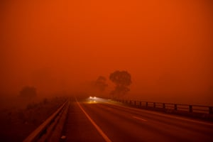 The sky turns dark and orange from the Border Fire before midday, south of Bega on the New South Wales south coast as the fire front creeps north toward Eden.