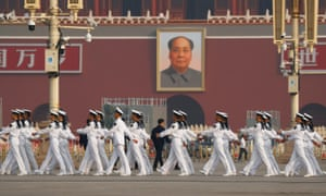 Soldiers march in Tiananmen Square before the image of Mao Zedong.