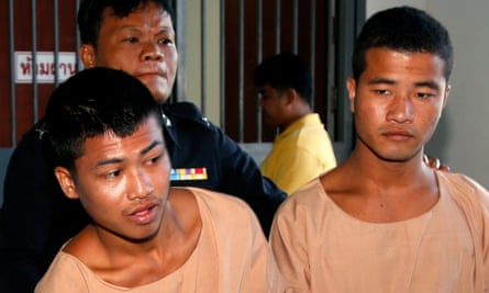 Wai Phyo (left) and Zaw Lin are escorted by a Thai police officer after being sentenced to death.