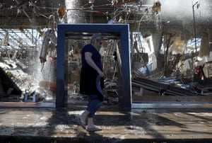 Dallas, US: A woman walks in front of a damaged Talbots store after a tornado struck on Sunday night, causing major damage to homes, businesses and schools.