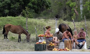 A family of farmers selling mangoes wait for customers at the side of a road on the outskirts of Havana.