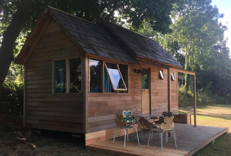 A wooden cabin at Bot-Conan Lodge, Beg-Meil, France, with chairs and table on its verandah
