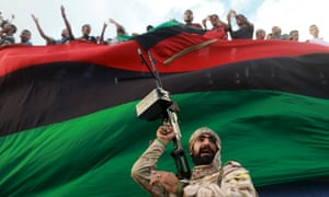 In Benghazi, Libya, an armed guard protects people demonstrating against candidates for a a national unity government