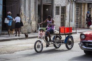 A man rides a tricycle decorated with a picture of Castro