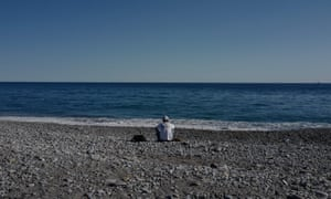 A migrant sits on a beach in Ventimiglia on 5 August, 2020, after the Ventimiglia Red Cross centre was closed a few days prior, resulting in migrants being left to themselves in the Italian town.
