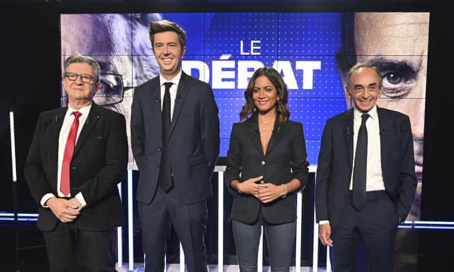 Jean-Luc Mélenchon, left, and Éric Zemmour, right, pose with the French journalists and hosts Maxime Switek and Aurélie Casse  prior to the debate in Paris.