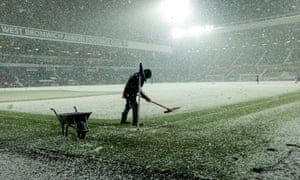 Grounds staff clear the snow off the pitch.