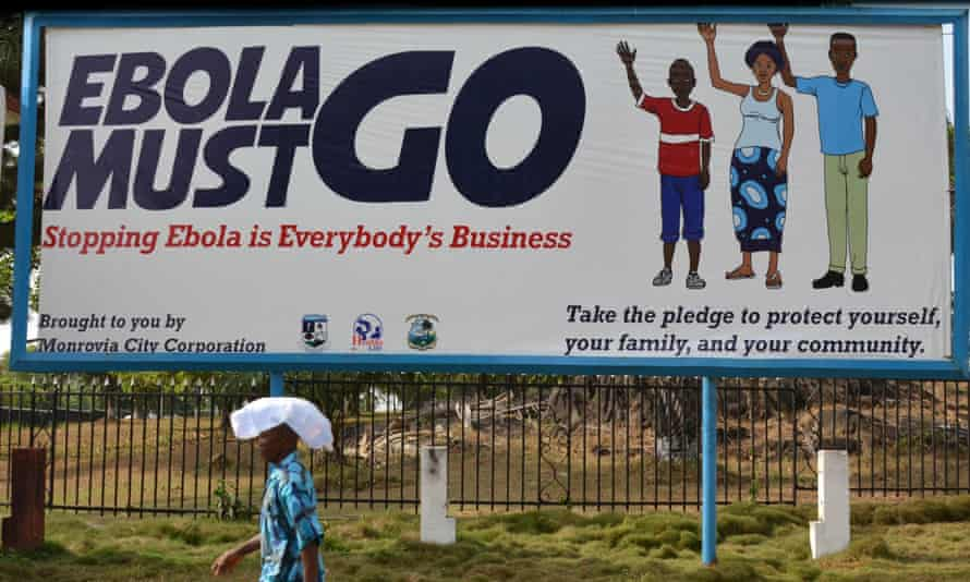 A man walks past an ebola campaign banner in Monrovia, Liberia.