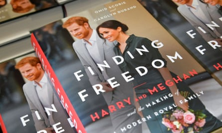 Copies of the book Finding Freedom stacked in a pile. The book's cover image is of Harry and Meghan, who is holding a bunch of pink flowers